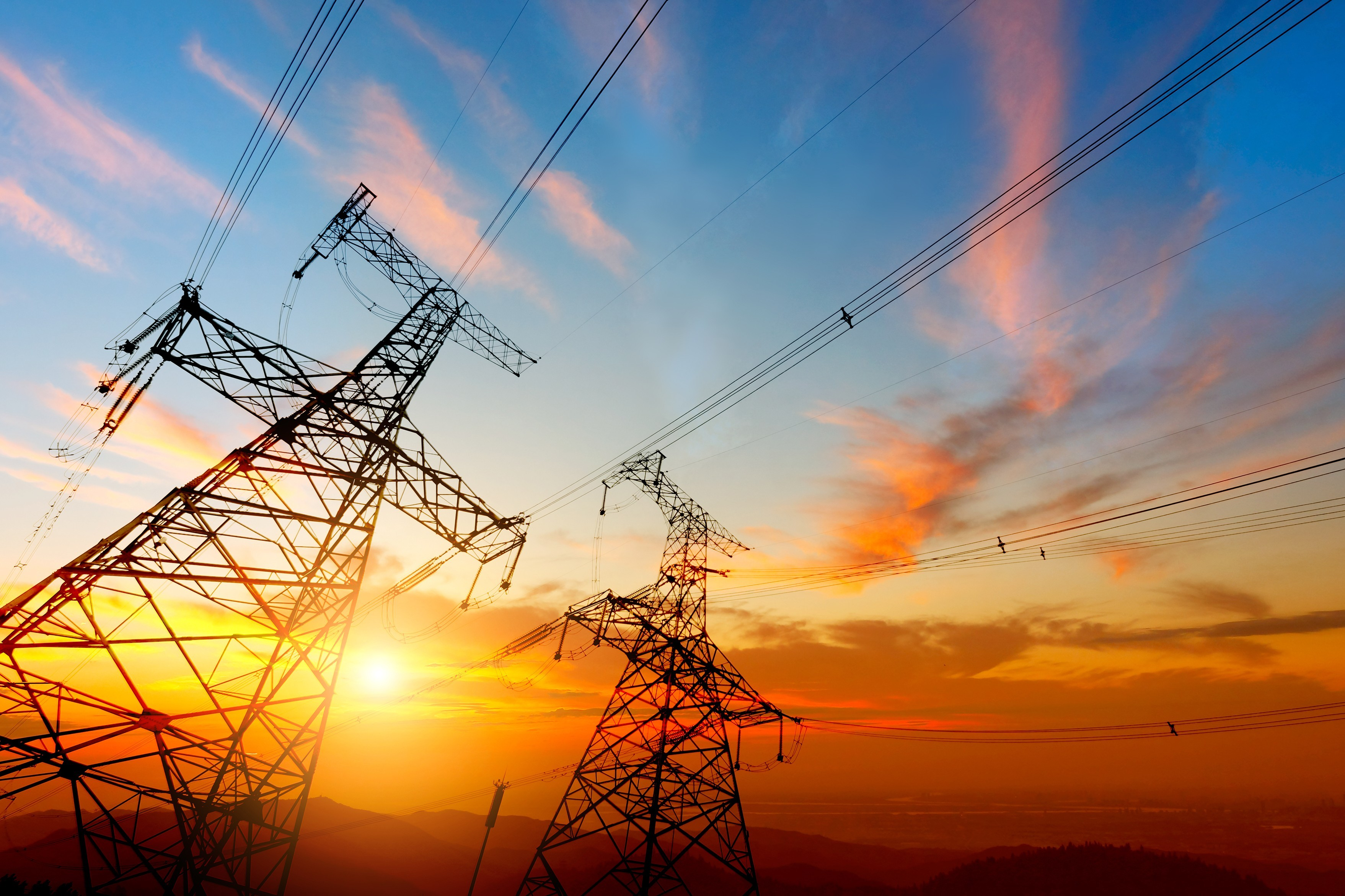 Two Transmission Towers with lines infront of a sunset
